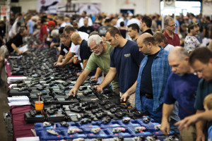 epa03323086 Shoppers examine handguns on display for sale at The Nation's Gun Show held in the Dulles Expo Center in Chantilly, Virginia, USA, 28 July 2012. Gun sales have risen in the U.S. in the wake of the movie theatre shooting massacre in Aurora, Colorado on 20 July. EPA/JIM LO SCALZO